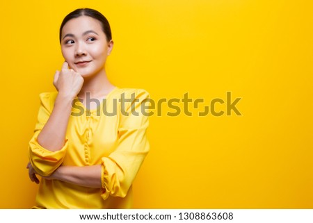 Happy woman thinking and standing isolated over yellow background #1308863608