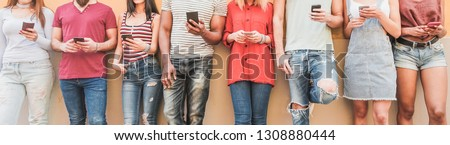 Teenager friends watching videos on smartphones  - Millennials generation addiction to new technology trends - Concept of youth, commute, tech, social and friendship - Main focus on center hands #1308880444