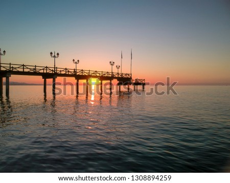 Sun peeping through Marbella jetty at sunrise #1308894259