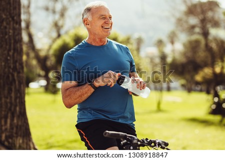 Senior man in fitness wear drinking water sitting on his bicycle. Cheerful senior fitness person taking a break during cycling in a park. #1308918847
