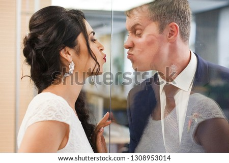 The groom and the bride are reflected in glass at office. #1308953014