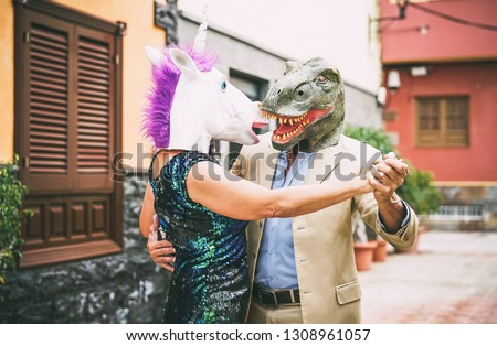 Crazy couple dancing and wearing dinosaur t-rex and unicorn mask - Senior elegant people having fun masked at carnival parade - Absurd, eccentric, surreal, fest and funny masquerade concept #1308961057