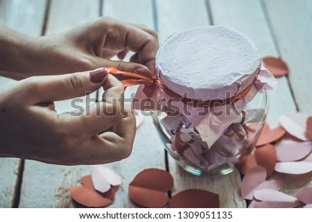Lover's day. Hand opening glass jar or date Jar with desires or wishes. Red paper hearts at background. #1309051135