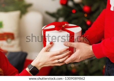 Happy Valentine's Day. Beautiful young couple at home. Groom holding a gift box. Love concept . #1309089862