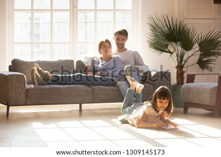 Happy parents relaxing on couch in comfort light living room while little kid child daughter playing on warm floor drawing with colored pencils, family having fun together, underfloor heating concept #1309145173