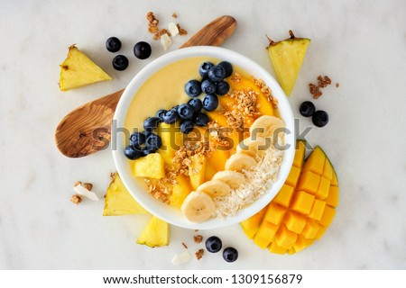 Healthy pineapple, mango smoothie bowl with coconut, bananas, blueberries and granola. Above view scene on a bright background. #1309156879