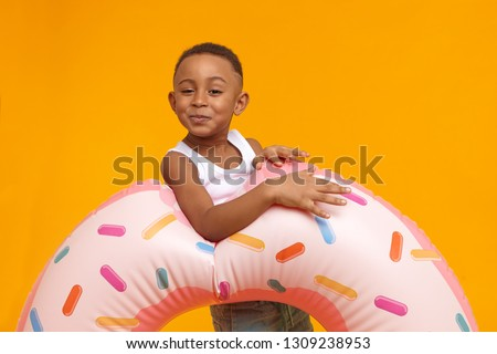 Happy funny little boy of African appearance having fun, posing at yellow wall with inflatable pink doughnut circle, going to beach. Adorable black male child carrying swimming ring, enjoying summer