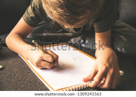 Close up bottom view of a young boy drawing a face on a white sheet. Kid hold a pencil and draw something, warm orange light at home. Children writing on a paper. Teen drawing sitting on a sofà #1309241563