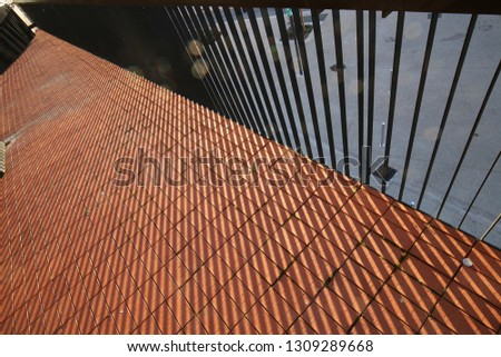 Abstract view of the tile floor of a balcony with part of a metallic barrier. Geometric design with parallel grey lines created by shadows.    #1309289668