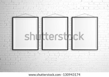 three black frames on brick wall