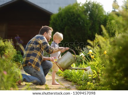 Middle age man and his little son watering flowers in the garden at summer sunny day. Gardening activity with little kid and family Royalty-Free Stock Photo #1309457098
