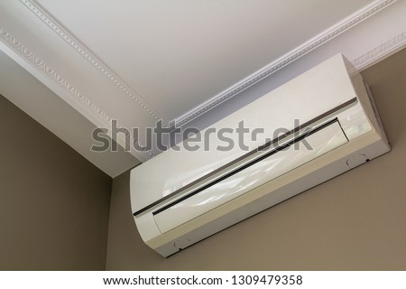 Cool air conditioner installed in room interior on white ceiling and light walls copy space background. Climate control, comfortable home concept. #1309479358