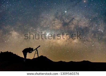 Silhouette of man watching star in telescope against  milky way galaxy with stars and space dust in the universe. #1309560376