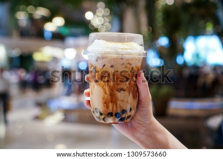 Bubble Milk tea, man holding a plastic cup of bubble/boba milk tea with brown sugar and topped with milk foam. Blurred background. #1309573660