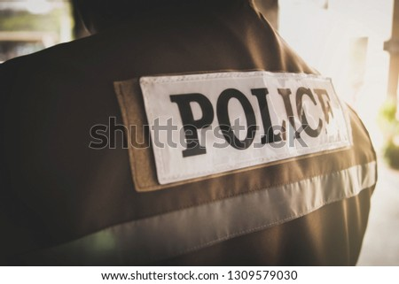 Vintage male police officers wear a khaki vest with a police message on the back : Horizontal View    #1309579030
