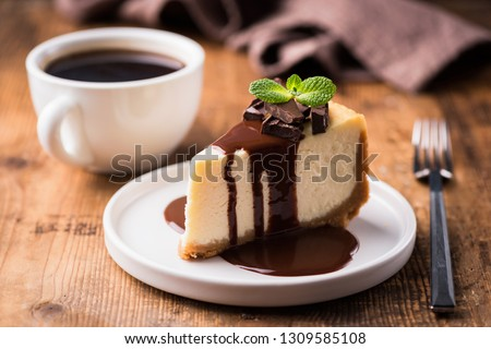 Cheesecake with chocolate sauce and cup of black coffee on a wooden table. Tasty snack or coffee time with slice of cake #1309585108