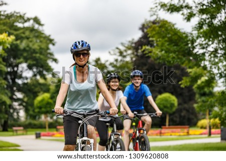 Healthy lifestyle - people riding bicycles in city park  #1309620808