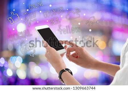 Woman hands holding and using smartphone with blank screen for your text or advertising on blurred shopping mall lighting background with freehand doodle graphic. #1309663744