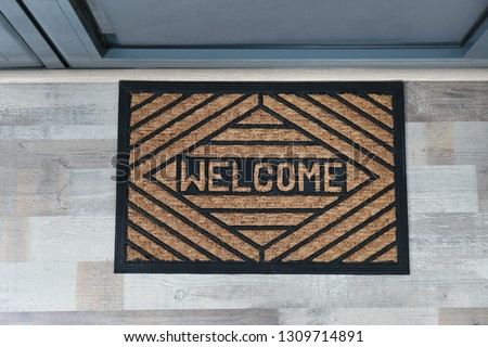 New clean mat with word WELCOME near entrance door, top view #1309714891