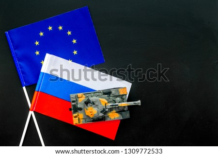 War, confrontation concept. European Union, Russia. Tanks toy near european and russian flag on black background top view copy space #1309772533
