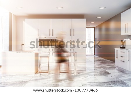 Woman in interior of modern kitchen with beige walls, marble floor, white bar with stools and white cupboard with two built in ovens. Toned image blur #1309773466