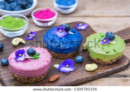 various raw vegan cakes with matcha, acai, butterfly pea tea, fresh berries, mint and nuts. healthy vegan food concept. close up #1309785196