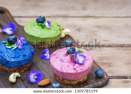 homemade raw vegan colorful cakes with matcha, acai and butterfky pea tea, fresh berries, mint, nuts. healthy vegan food concept. close up #1309785199