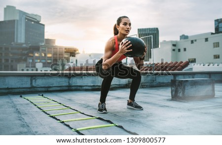 Female athlete doing squats holding a medicine ball standing on a rooftop. Woman doing workout using medicine ball with an agility ladder by her side on rooftop. #1309800577