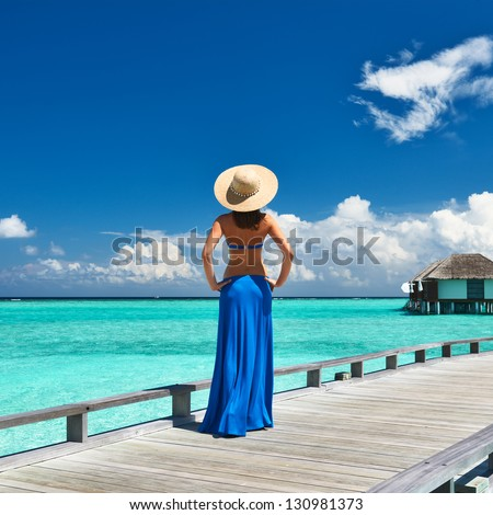 Woman on a tropical beach jetty at Maldives #130981373
