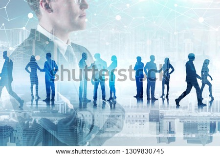 Side view of confident businessman standing with crossed arms in city with his colleagues silhouettes and polygonal network in the sky. Toned image double exposure #1309830745