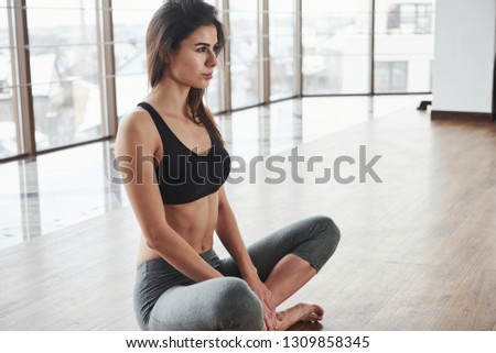 Isolated portrait. Relaxed cute young girl sits on the floor in gym with big windows. #1309858345