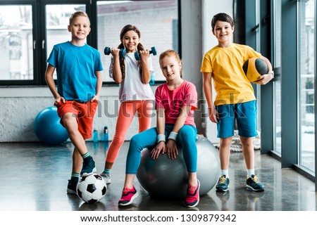 Laughing preteen kids posing with sport equipment #1309879342