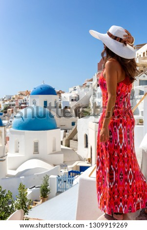 Attractive traveler tourist woman in red dress enjoys the view to the blue domed churches of Oia on the island of Santorini, Greece, during summer vacation time #1309919269