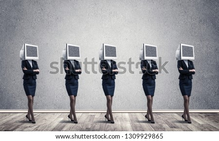 Business women in suits with monitors instead of their heads keeping arms crossed while standing in a row in empty room with gray wall on background. #1309929865