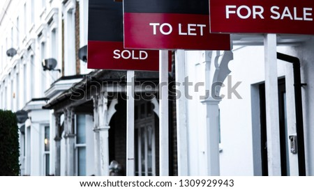 Estate agent  'for sale', 'to let' and 'sold' signage boards of street of terraced houses