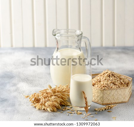 The concept of a vegetarian diet. Oat milk in the glass with jug of oat milk and oat and oat ears. Light background #1309972063