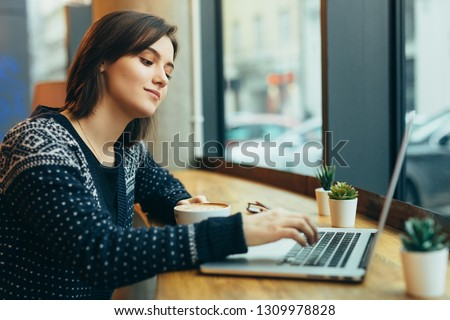 Woman Look Around And Smile While Work In Cafe On Her Laptop. Portrait Of Stylish Smiling Woman In Winter Clothes Work At Laptop. Female Bussiness Style With Sun. - Image #1309978828