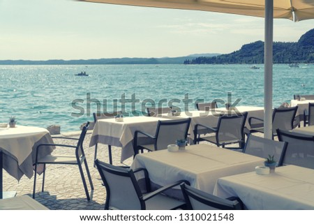 Cafe on the edge of the sea or lake, tables covered with white tablecloths with ashtrays and decorative pots on a sunny summer day, standing in the shade of an umbrella #1310021548