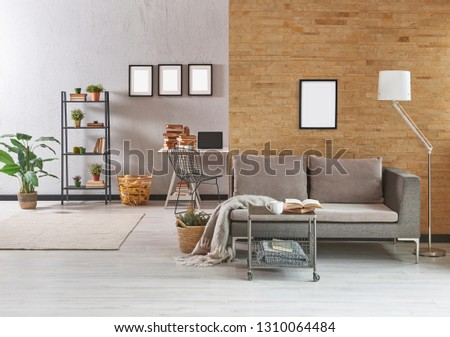 Grey living room, dark yellow brick wall, grey furniture sofa and modern home decoration. Frame picture lamp and middle table style. carpet and vase of plant in the room. #1310064484
