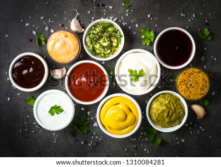 Set of sauces - ketchup, mayonnaise, mustard soy sauce, bbq sauce, pesto, chimichurri, mustard grains and pomegranate sauce on dark stone background. Top view. #1310084281