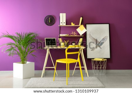 Stylish workplace with modern laptop near color wall Royalty-Free Stock Photo #1310109937