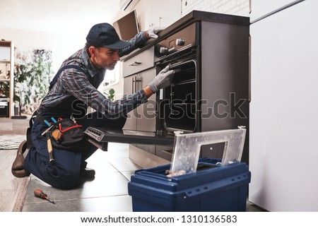 Don't delay with repair. Close-up of repairman examining oven with screwdriver in kitchen with tool case Royalty-Free Stock Photo #1310136583