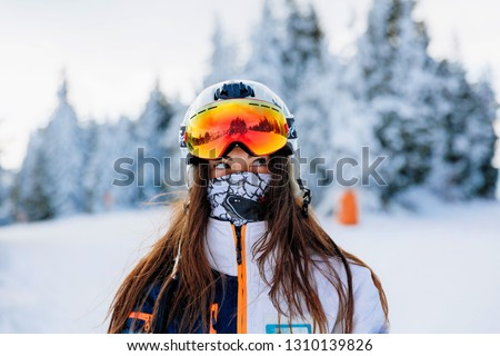 Ski, skier, sun and winter fun - woman enjoying ski vacation. Sport, leisure and people concept - happy young woman in ski goggles outdoors. Ski resort - Image #1310139826