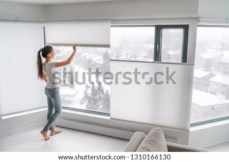 Woman opening home curtains in urban condo. Modern top down bottom up privacy cellular shades on apartment window keeping heat in winter with honeycomb blind curtain. Cordless pleated shades. #1310166130
