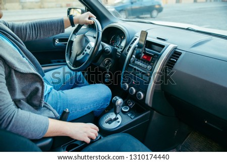 young man driving car. coffee cup in cup holder. lifestyle #1310174440