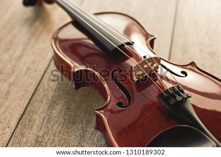 Close up view of beautiful classical violin lying on wooden background. Musical instruments. Music equipment. Music background #1310189302
