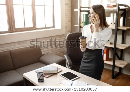 Young businesswoman stand at table in room. She talk on phone and look at window. Model hold cup of coffee. #1310203057