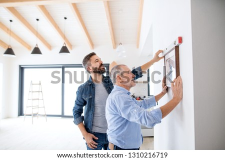 A senior man helping his son hanging up pictures on wall, a new home concept.