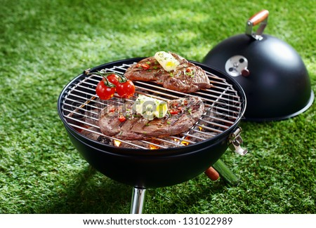 High angle view of two succulent steaks cooking on a barbecue over the hot coals on a green lawn outdoors