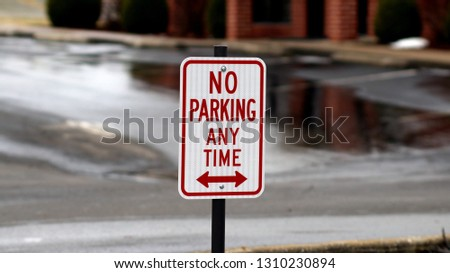 no parking any time sign with arrows pointing in both directions